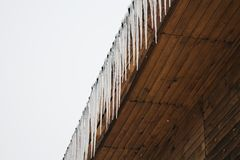 Frozen icicles on the roof of the wooden house, top floor wooden mansion. Icy weather winter scene. Frozen icicles on the wooden roof, top floor wooden mansion stock photography