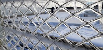 The frozen icicles of sea water. Icy handrails of the embankment in Odessa, Ukraine. cold icicle of winter sea. Winter landscape with icy fence on the background royalty free stock photo