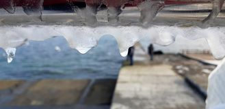 The frozen icicles of sea water. Icy handrails of the embankment in Odessa, Ukraine. cold icicle of winter sea. Winter landscape with icy fence on the background stock photos