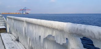 The frozen icicles of sea water. Icy handrails of the embankment in Odessa, Ukraine. cold icicle of winter sea. Winter landscape with icy fence on the background stock image