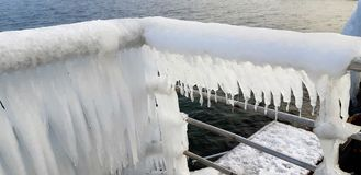 The frozen icicles of sea water. Icy handrails of the embankment in Odessa, Ukraine. cold icicle of winter sea. Winter landscape with icy fence on the background stock photo