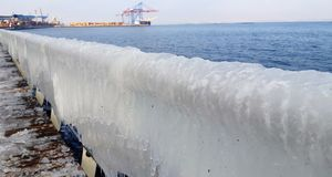 The frozen icicles of sea water. Icy handrails of the embankment in Odessa, Ukraine. cold icicle of winter sea. Winter landscape with icy fence on the background royalty free stock photos