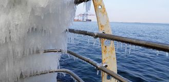 The frozen icicles of sea water. Icy handrails of the embankment in Odessa, Ukraine. cold icicle of winter sea. Winter landscape with icy fence on the background royalty free stock images