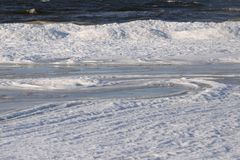 Frozen, icy Baltic Sea coast 10. Baltic Sea coast covered with a lot of shining ice cubes like diamonds on the sand and water surface. Waves are frozen in the stock photography