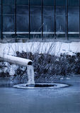 Frozen industry. Frozen sewer pipe next to a factory Royalty Free Stock Images