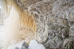 Icy waterfall scape. Frozen Jagala river waterfall long exposure. Rocks covered by ice and snow, long stalactites of ice Stock Photography