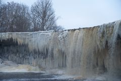 Icy waterfall scape. Frozen Jagala river waterfall long exposure. Rocks covered by ice and snow, long stalactites of ice Royalty Free Stock Image