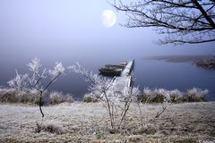 Frozen Lake. Stunning light as the Moon shines through the Fog and highlights the atmospheric and peaceful frost coated scene in Northumberland, England in the Stock Image