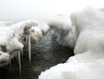 Frozen lake. Snowdrifts, ice and icicles on a frozen lakeshore in February Royalty Free Stock Image