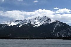 Frozen Lake. A snow capped mountain peak towers over a frozen lake Stock Photos