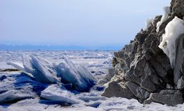 Frozen lake. Baikal in winter. Hill covered by snow Royalty Free Stock Photos