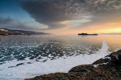 Frozen Lake Baikal. Beautiful stratus clouds over the ice surface on a frosty day. Natural background royalty free stock photo
