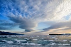 Frozen Lake Baikal. Beautiful stratus clouds over the ice surface on a frosty day. Natural background stock photo