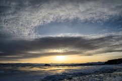 Frozen Lake Baikal. Beautiful stratus clouds over the ice surface on a frosty day. Natural background royalty free stock image