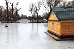 Frozen lake with bridge and wooden house Stock Photos