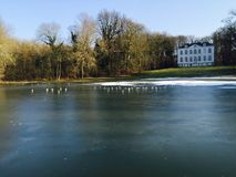 Frozen lake in Brussels. This picture represents a frozen lake in Brussels during the winter, with a beautiful, typical european building in background. It`s a Royalty Free Stock Image