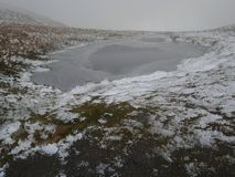 A frozen lake. Carl Side tarn on a mountain fell in the Lake District frozen in different shades Royalty Free Stock Photos