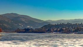 Frozen lake covered with snow, beautiful mountains can be seen in the distance royalty free stock images