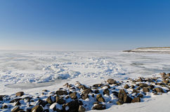 Frozen lake with crushed ice sheet and rocks Stock Photo