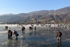 The frozen lake Endine in the Bergamo area - Italy. Sunday, January 8, 2017-Lake Endine-Bergamo-Lombardia-Italy-A crowd of unidentified people enjoy walking on royalty free stock photos