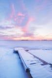 Frozen lake and fishing dock at sunrise Stock Photo