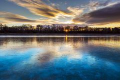 Frozen lake in the forest colored clouds. Stock Image
