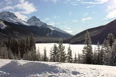 A frozen lake in front of a mountain in the rockies under blue s Royalty Free Stock Image