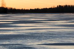 Frozen lake. At twilight in winter, golden sunset royalty free stock photography