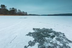 Frozen lake with hole in ice made by fisherman Royalty Free Stock Image