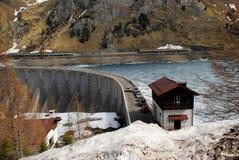 Frozen Lake and Dam, The Italian Dolomites. Frozen Lake Fadaia (Lago di Fadaia) thawing in the spring at the western Italian Dolomites Stock Image
