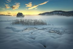 Frozen lake Jonsvatnet near Trondheim, Norway. Sunset light over gathering fog stock images
