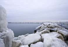 Frozen Lake Michigan Pier. Ice and snow cover the Holland pier and  walkway on a cold winter day in Michigan Stock Photo