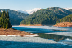 Frozen lake in the mountains. Early in the spring Stock Images