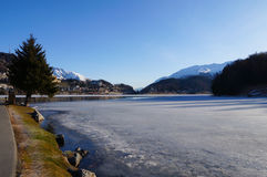 Frozen lake and the mountains covered by snow, Switzerland Stock Photos