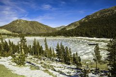 Frozen lake near Tuolumne Meadows, Yosemite National Park, California, USA. The skies are clear and bright Stock Photo