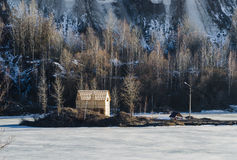 Frozen lake with one house in a mountain land Royalty Free Stock Images