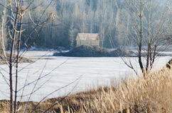 Frozen lake with one house in a mountain land Stock Images