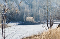 Frozen lake with one house in a mountain land Stock Photography
