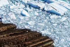 Frozen Lake and Rocky Shorline. Ice Chunks on the Edge of a Frozen Lake. Ice chunks are bright blue in color from a glacier stock image