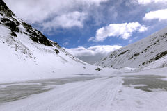 Frozen lake between snow mountains Stock Photography