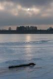 Frozen lake at sunrise or sunset. Winter tranquil landscape. Frozen lake at sunrise landscape. Beautiful landscape of winter lake in Mazury lake district Stock Image