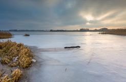 Frozen lake at sunrise or sunset. Winter tranquil landscape. Royalty Free Stock Photo