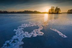 Frozen lake at sunrise or sunset. Winter tranquil landscape. Stock Photography