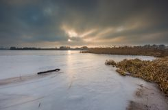 Frozen lake at sunrise or sunset. Winter tranquil landscape. Royalty Free Stock Photos