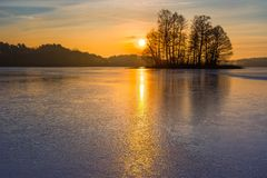 Frozen lake at sunrise or sunset. Winter tranquil landscape. Stock Images