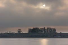 Frozen lake at sunrise or sunset. Winter tranquil landscape. Frozen lake at sunrise landscape. Beautiful landscape of winter lake in Mazury lake district Stock Photos