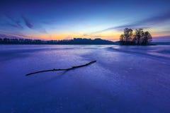 Frozen lake at sunrise or sunset. Winter tranquil landscape. Stock Photo