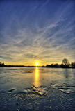 Frozen lake at sunset. The picture shows a frozen lake at sunset stock image