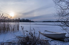 Frozen lake and sunset. Boat on frozen lake with sunset Stock Photos
