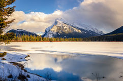 Frozen Lake with a Towering Mountain in Background at Sunset. Frozen Vermilion Lake with Mount Rundle in Background at Sunset. Banff, AB, Canada Stock Images